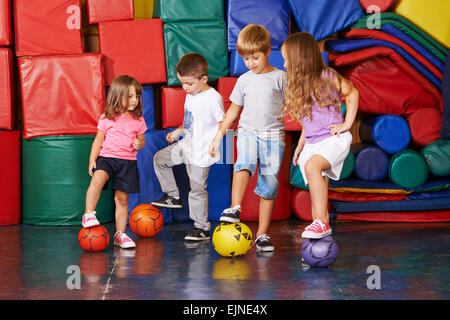 Four children playing soccer in gym of kindergarten together - Stock Photo
