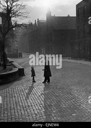 Edinburgh street scenes Policeman talking to lost child on a cobbled street in Edinburgh, Scotland. Scenic Atospheric - Stock Photo