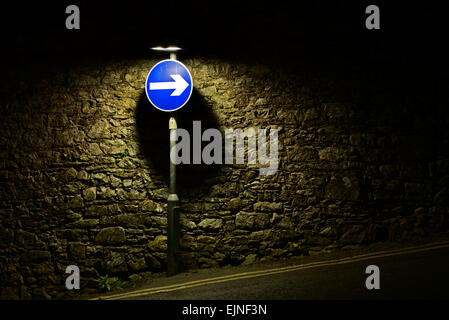 Road spot spotlit against a stone wall - Stock Photo