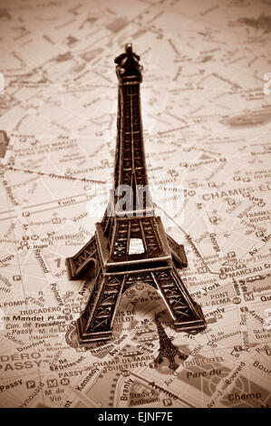 a reproduction of the Eiffel Tower on a map of Paris, with sepia toning - Stock Photo