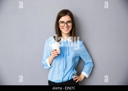 Portrait of a cheerful businesswoman holding cup with coffee over gray background. Wearing in blue shirt and glasses. - Stock Photo