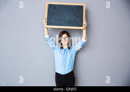 Happy woman standing with billboard over gray background. Wearing in blue shirt and glasses. Looking at camera - Stock Photo