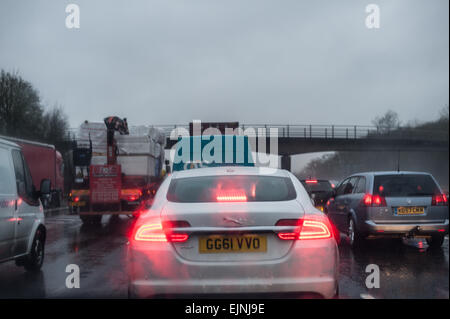 dreary wet rush hour journey standstill on motorway carriage stationary cars lorries with tail rear brake lights - Stock Photo