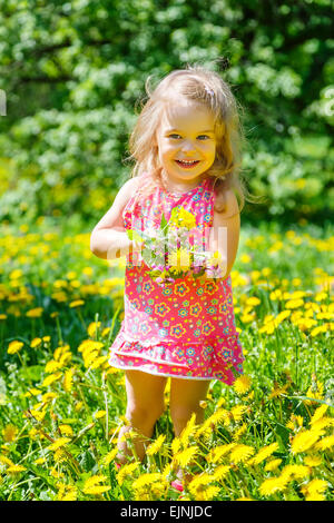 Little girl with bouquet in the park - Stock Photo