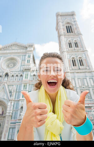 Happy young woman showing thumbs up in front of duomo in florence, italy - Stock Photo