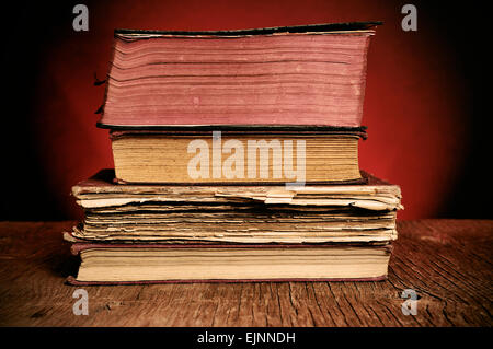 a pile of worn-out old books on a rustic wooden table - Stock Photo