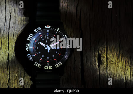 Tritium military watch on old wood - Stock Photo