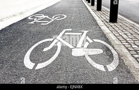 White painted bike path signs on asphalt. - Stock Photo