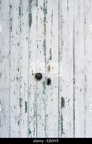 Old painted white wooden doors with peeling paint texture - Stock Photo