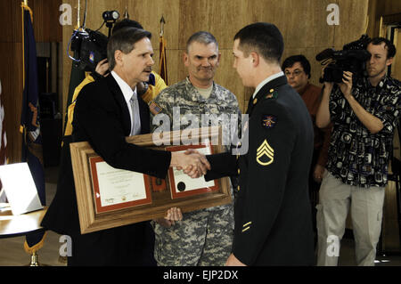 Governor John Hoeven shakes hands with U.S. Army Staff Sgt. Justin Lampert while presenting him with the Soldier's - Stock Photo