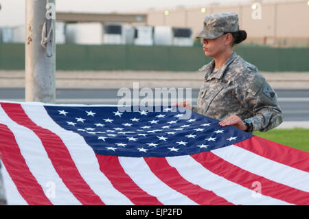 A Soldier on flag detail prepares to fold Old Glory as part of a daily reveille ceremony held Oct. 24 at Camp Arifjan, - Stock Photo