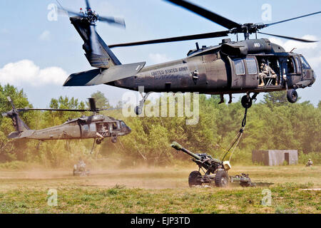 UH-60 Black Hawk helicopters airlift 105 mm howitzers to a predetermined area on Fort Drum, N.Y., July 18, 2012. - Stock Photo