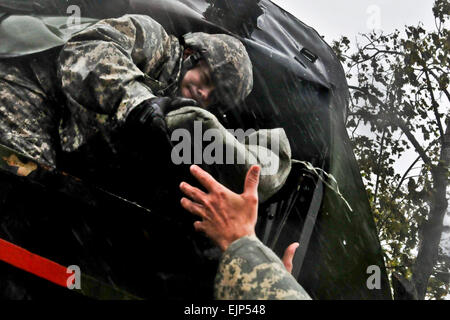 New Jersey Army National Guardsman Staff Sgt. Kenneth Williams hands sand bags out the back of a M35 2¬Ω ton cargo - Stock Photo