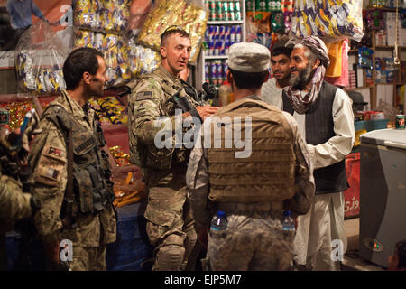 An Afghan National Civil Order Police officer speaks to a local shop owner during a mission led by U.S. Army soldiers - Stock Photo