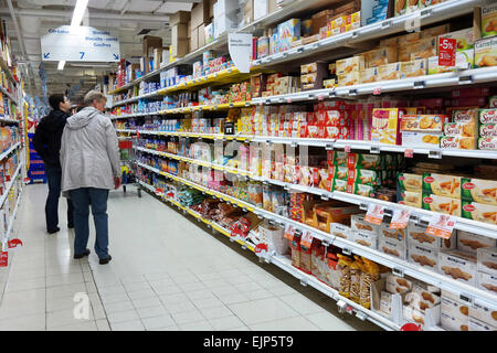 WALLONIA, BELGIUM - OCTOBER 2014:  Shopping in the cookies section in a Carrefour Hypermarket - Stock Photo