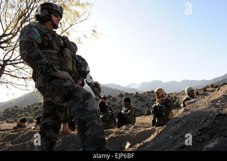 A U.S. Army Special Forces Soldier, from Special Operations Task Force-East,  watches Afghan Commandos, from 2nd - Stock Photo