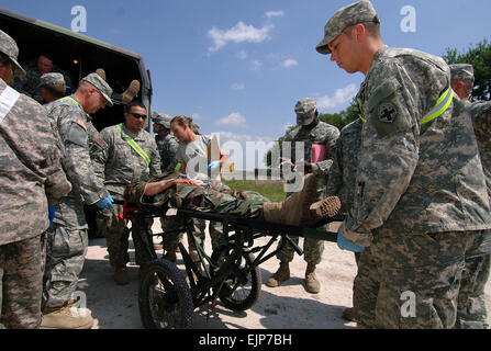 Soldiers from the 441st Ground Ambulance Company and the 345th Combat Support Hospital off-load a Soldier injured - Stock Photo