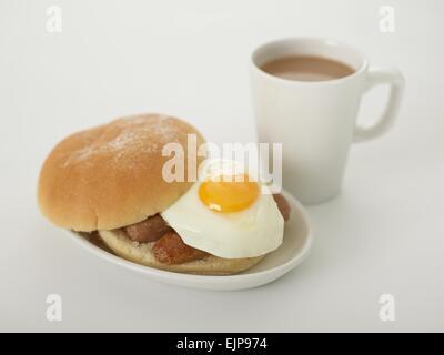 sausage fried egg bap bread bun floured breakfast mug of tea on a white background - Stock Photo