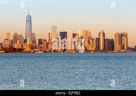 Statue of Liberty, One World Trade Center and Downtown Manhattan across the Hudson River, New York, United States - Stock Photo