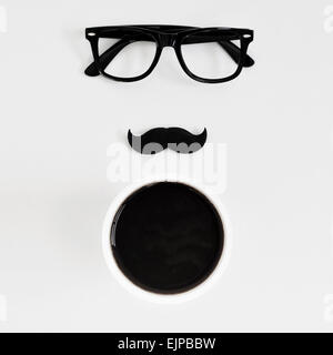 high-angle shot of a white table with a pair of black plastic-rimmed eyeglasses, a fake moustache and a cup of coffee, - Stock Photo
