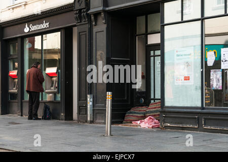 Man withdrawing cash from a bank cash machine next to a homeless persons bed in a disused shop doorway - Stock Photo