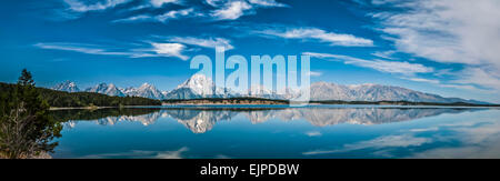 Panoramic image of stunning mirror-like reflections of the Grand Tetons in Jackson Lake, Wyoming, USA with azure - Stock Photo