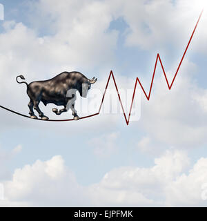 Bull market risk financial concept as a heavy bullish beast walking on a high tightrope shaped as a stock market - Stock Photo