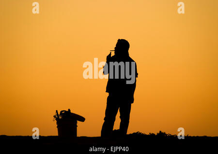 A man smoking a cigarette is silhouetted against an orange sunset sky. - Stock Photo