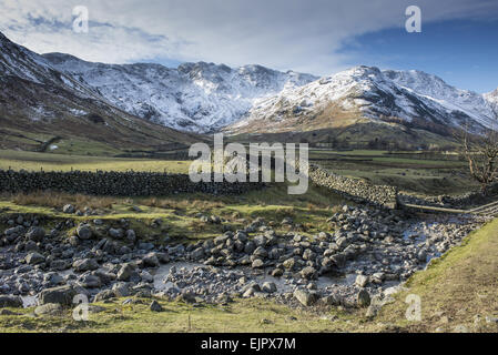 View across rocky stream, drystone walls and valley pasture towards snow covered fell, Langdale Fell, Great Langdale, - Stock Photo