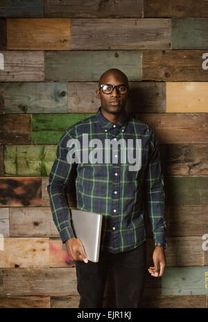Portrait of serious young african man with a laptop looking at camera while standing against a wooden wall in office. - Stock Photo
