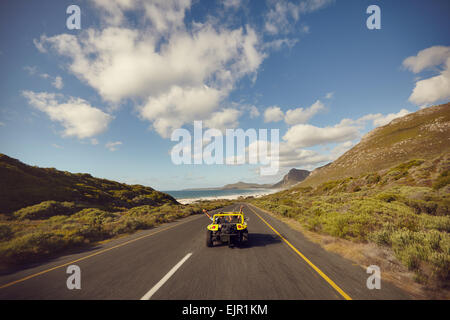 Rear view shot of a young couple driving down an open road excited to be on a roadtrip. Happy couple driving a car - Stock Photo