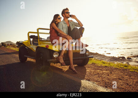 Portrait of young couple sitting on a their car by the sea shore, with man using mobile phone. Couple on summer - Stock Photo