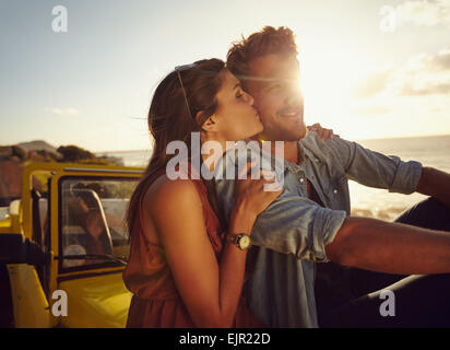 Romantic young couple sitting on the hood of their car while out on a roadtrip. Beautiful young woman kissing her - Stock Photo