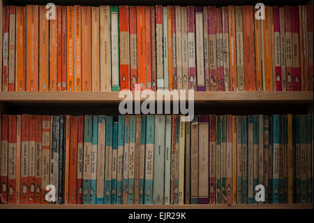Bookcase shelves full of a collection of vintage Penguin and Pelican Books - Stock Photo