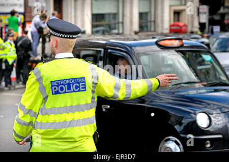 London, England, UK. Black cab drivers dispute, 2014. Police officer directing the traffic - Stock Photo