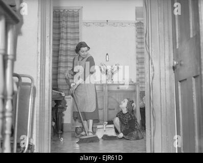 Stay at home mother Mrs Mary Mackenzie seen here bing helped in her household chores by her daughter Linda. 2nd - Stock Photo