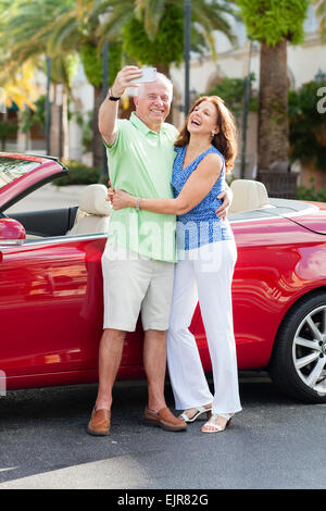 Older Caucasian couple taking cell phone photograph near convertible