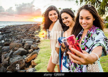 Pacific Islander women taking cell phone photograph near rocky beach - Stock Photo