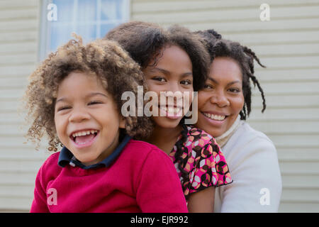 Pacific Islander mother and children hugging outdoors - Stock Photo