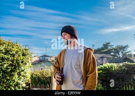 Caucasian man drinking beer in backyard