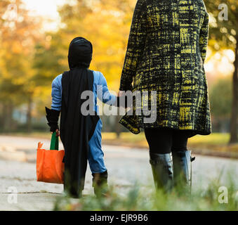 African American boy trick-or-treating with mother on Halloween - Stock Photo