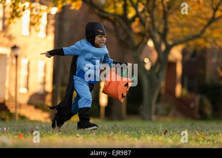African American boy trick-or-treating on Halloween - Stock Photo