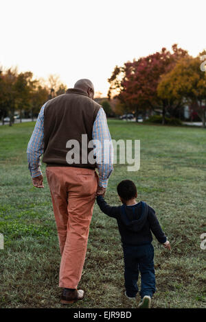 African American father and son walking in park - Stock Photo