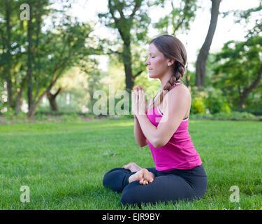 Caucasian woman meditating in park - Stock Photo