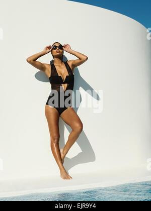 Mixed race woman in swimsuit wearing sunglasses near swimming pool