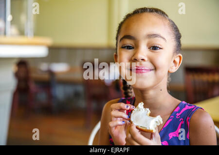 Mixed race girl eating bagel in cafe - Stock Photo