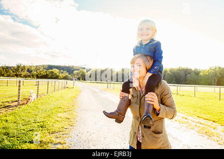 Caucasian mother carrying daughter on shoulders on rural road - Stock Photo