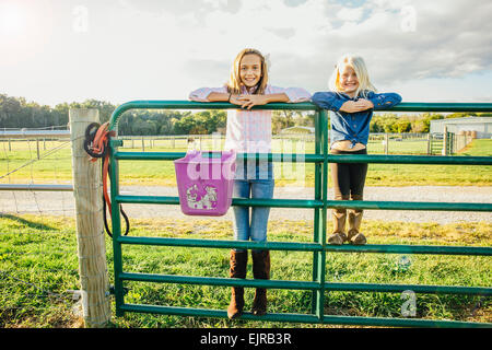 Caucasian girls standing on fence on ranch - Stock Photo