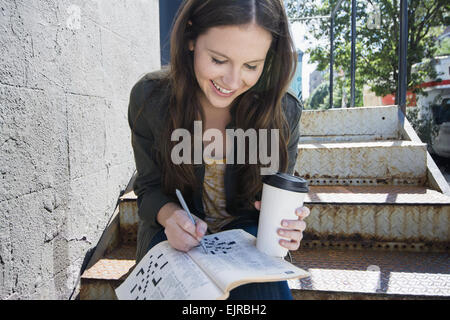 Caucasian woman doing crossword and drinking coffee on front steps - Stock Photo