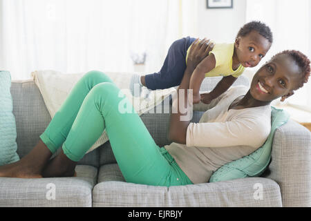 Black mother and son playing on sofa - Stock Photo